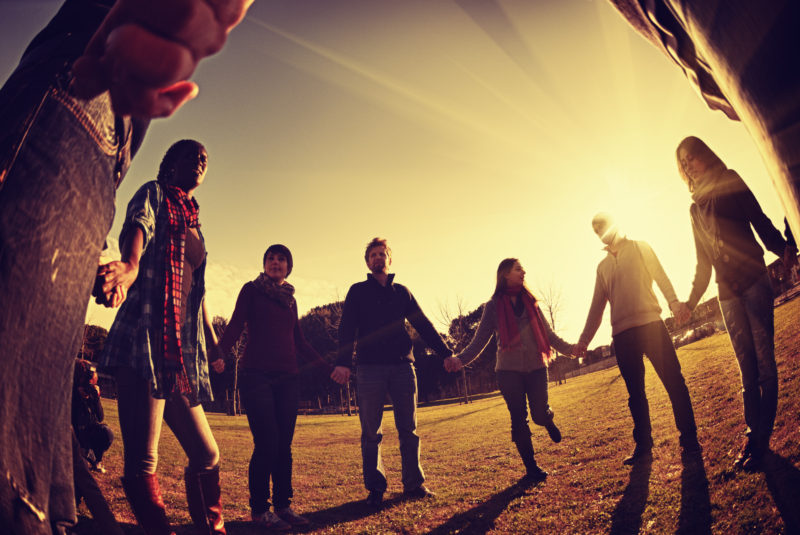 a group of millennials standing in a circle holding hands with bright sunlight in background