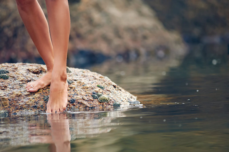 entrepreneur metaphore of person standing on a rock dipping their toes in water