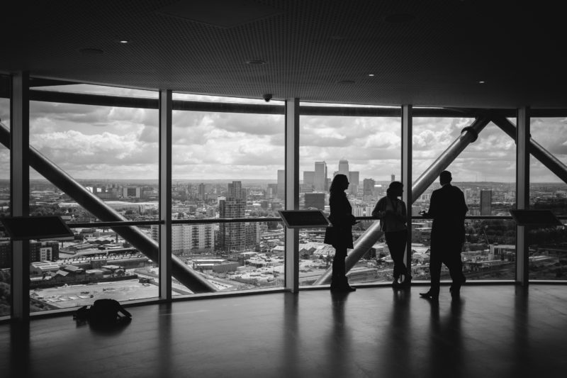 black and white city photography; silhouette of three people in building looking out to city